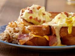 Benedict eggs served on a grilled cheese sandwich with bacon