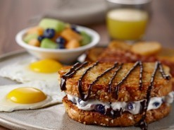 Combo eggs served with a crispy blueberry and cream cheese french toast sandwich